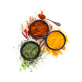 Spices: Indian food. Ground turmeric, chili pepper powder and dried parsley in black bowls shot from above on white background. The composition is at the center of the frame. High key DSRL studio photo taken with Canon EOS 5D Mk II and Canon EF 100mm f/2.8L Macro IS USM.