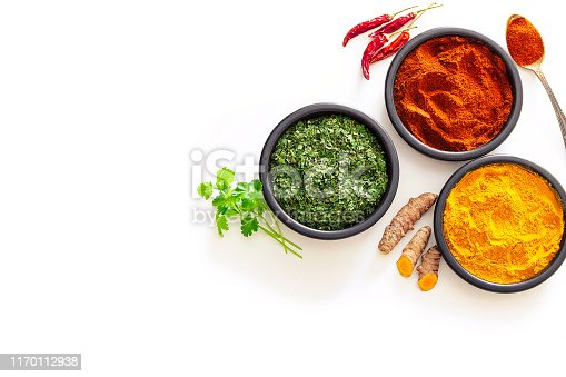 Spices: Indian food. Ground turmeric, chili pepper powder and dried parsley in black bowls shot from above on white background. The composition is at the right of an horizontal frame leaving useful copy space for text and/or logo at the left. High key DSRL studio photo taken with Canon EOS 5D Mk II and Canon EF 100mm f/2.8L Macro IS USM.