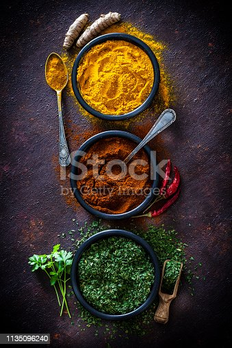 Spices: Indian food. Ground turmeric, chili pepper powder and dried parsley in black bowls shot from above on dark abstract background. Low key DSRL studio photo taken with Canon EOS 5D Mk II and Canon EF 100mm f/2.8L Macro IS USM.