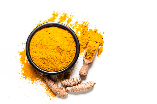 Spices: Top view of a black bowl filled with turmeric powder isolated on white background. A wooden serving scoop with turmeric powder is beside the bowl and turmeric powder is scattered on the table. Fresh organic turmeric roots are beside the spoon. Predominant colors are white and yellow. High key DSRL studio photo taken with Canon EOS 5D Mk II and Canon EF 100mm f/2.8L Macro IS USM.