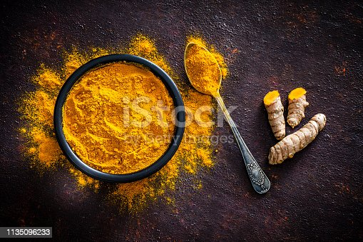 Spices: Top view of a black bowl filled with turmeric powder shot on abstract brown rustic table. A metal spoon with turmeric powder is beside the bowl and turmeric powder is scattered on the table. Fresh organic turmeric roots are beside the spoon. Predominant colors are brown and yellow. Low key DSRL studio photo taken with Canon EOS 5D Mk II and Canon EF 100mm f/2.8L Macro IS USM.