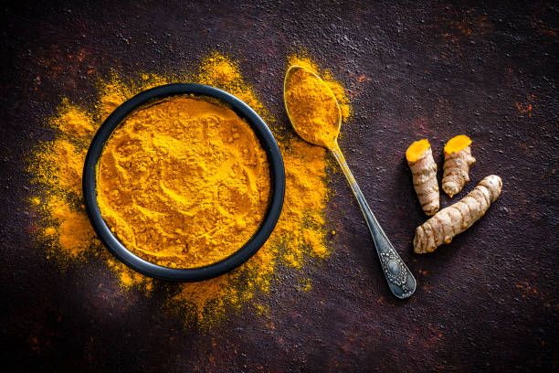 Spices: Turmeric roots and powder shot from above Spices: Top view of a black bowl filled with turmeric powder shot on abstract brown rustic table. A metal spoon with turmeric powder is beside the bowl and turmeric powder is scattered on the table. Fresh organic turmeric roots are beside the spoon. Predominant colors are brown and yellow. Low key DSRL studio photo taken with Canon EOS 5D Mk II and Canon EF 100mm f/2.8L Macro IS USM. curry powder stock pictures, royalty-free photos & images