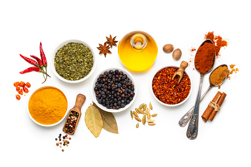 Cooking backgrounds: overhead view of several bowls and spoons with multicolored spices shot on white background. The composition includes dried oregano, turmeric, peppercorns, chili pepper cinnamon, bay leaves, cardamom, nutmeg and olive oil. High resolution 42Mp studio digital capture taken with Sony A7rII and Sony FE 90mm f2.8 macro G OSS lens