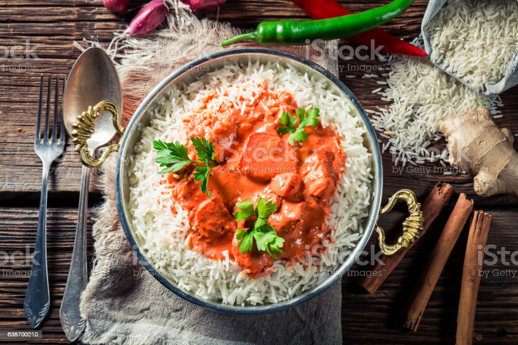 Spicy and sweet tikka masala with rice and sauce stock photo