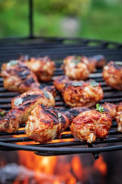 Würziges und leckeres gegrilltes Hühnerbein auf heißem Grill – Foto