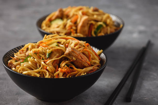 Spicy asian noodles with chicken and vegetables. stock photo