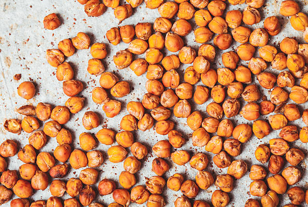 Spicy baked chickpeas Spicy baked chickpeas scattered on  baking paper chick pea stock pictures, royalty-free photos & images