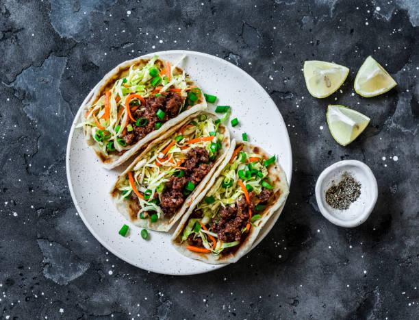 Würziges Rindfleisch und Kohl, Karotten eingelegt Salat-Tacos auf dunklem Hintergrund, oben – Foto