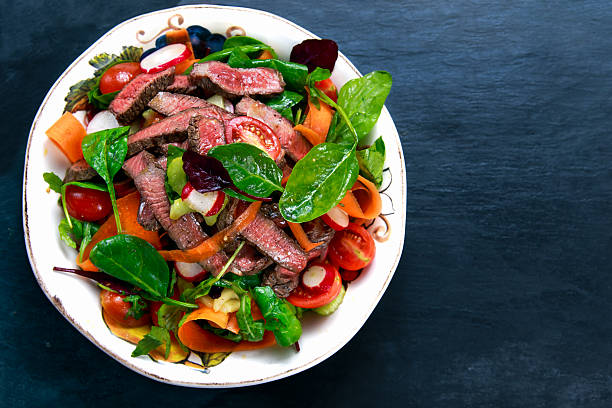 Spicy Beef Meat Salad with vegetables on blue stone. stock photo