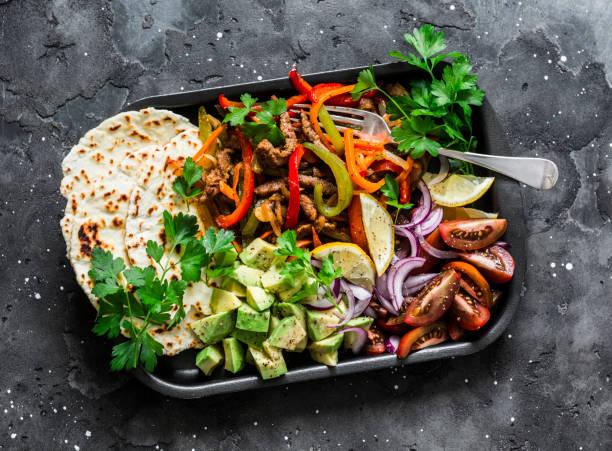 Würziges Rindfleisch, Gemüse, Avocado, Maistortillas fajitas auf einer Blechpfanne auf dunklem Hintergrund, Ansicht von oben. Köstlicher Snack, Tapas im mexikanischen Stil – Foto