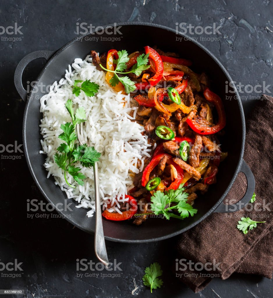 Spicy beef with vegetables and rice in a cast iron skillet on a dark background, top view. Asian style food stock photo
