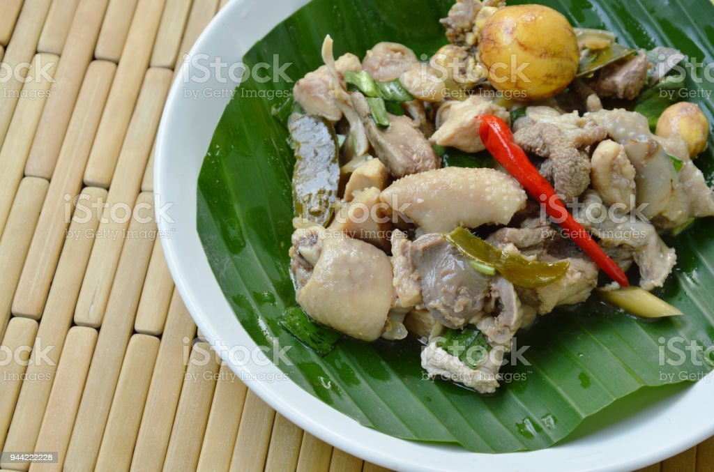 spicy boiled chicken and entrails salad on banana leaf stock photo