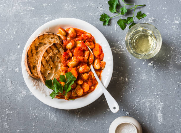 Spicy braised lima beans in tomato sauce and ciabatta toast on a grey background, top view. Delicious vegetarian lunch vegetable protein stock photo