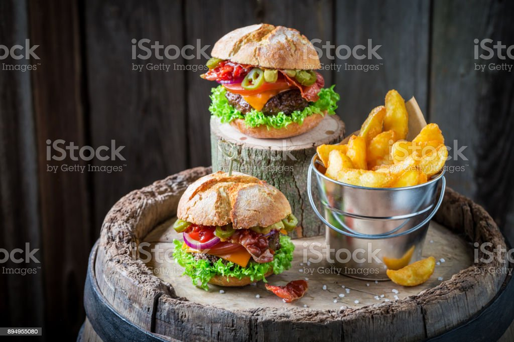 Spicy burger with onion, tomato and lettuce served with chips stock photo