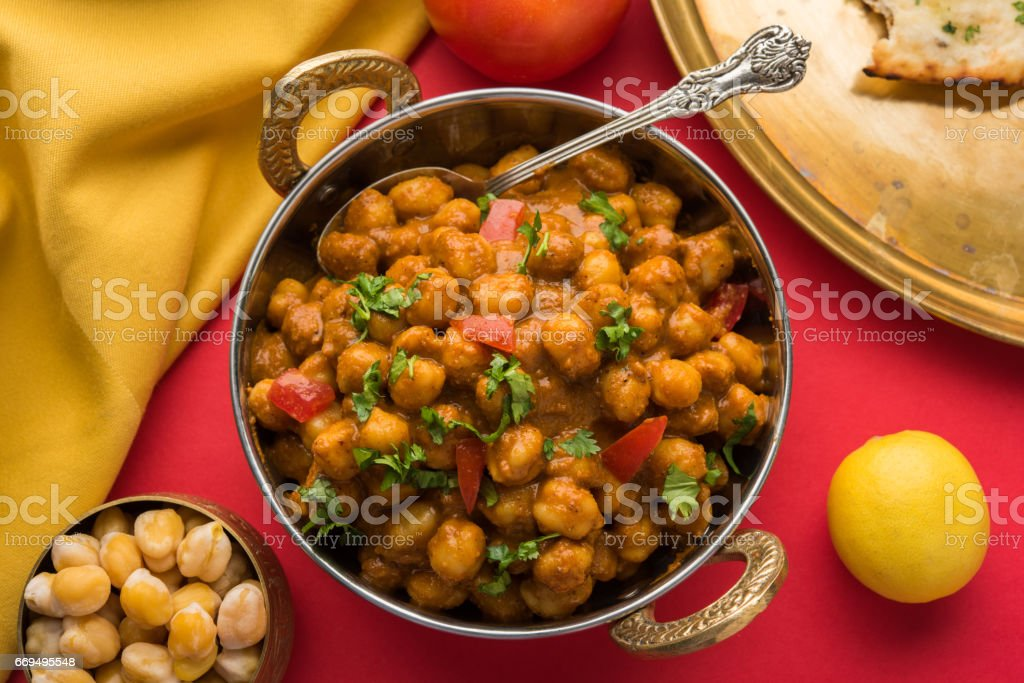 spicy chick peas curry or Chola Masala or Chana Masala or chole bhature or choley garnished with sliced onion and green coriander leaf, selective focus stock photo