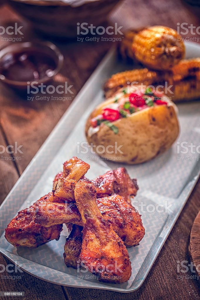 Spicy Chicken Wings with Baked Potato and Corn stock photo