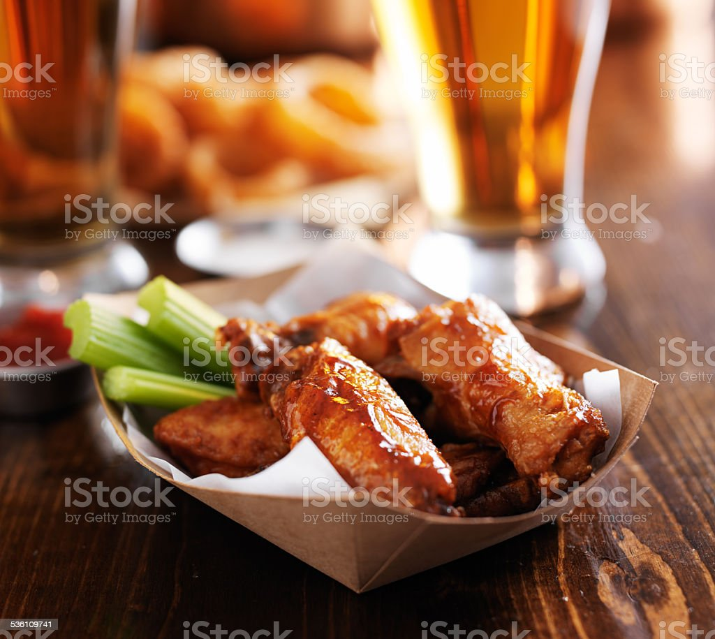 spicy chicken wings with beer in background stock photo