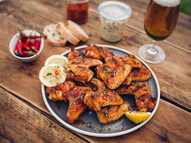 würzige chicken wings mit beilagen und einem glas bier - gewürz für gegrilltes hähnchen stock-fotos und bilder