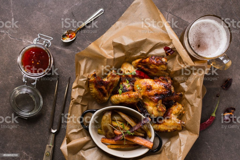 Spicy Chicken Wings with Hot Chili Jam, Baked Potatoes and Purple Carrots stock photo