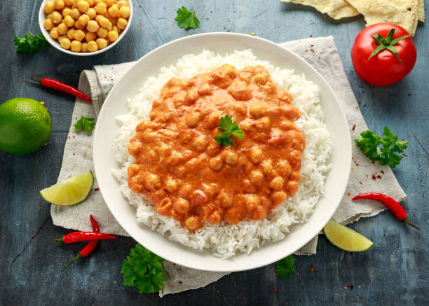 Spicy chickpeas curry with rice, tomato and Poppadoms in white plate. Healthy tasty vegetarian food stock photo