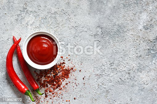 Spicy chili sauce with spices on a concrete background. View from above.