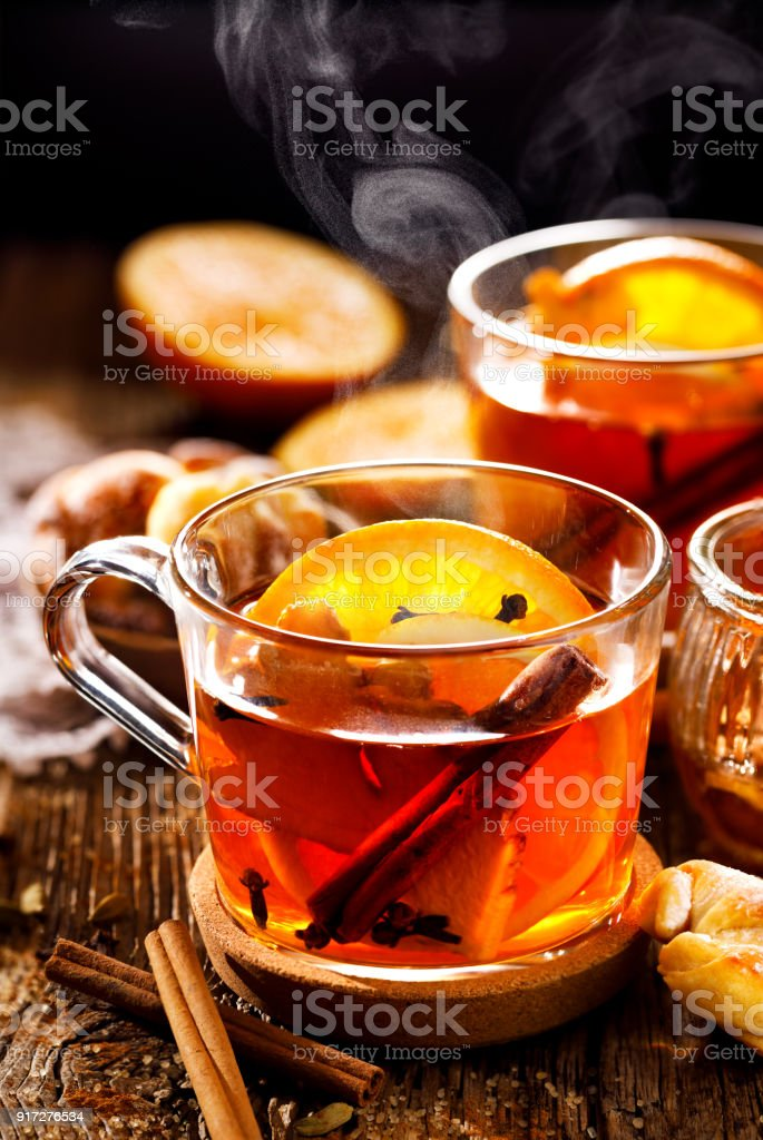 Spicy citrus hot tea with ginger, cloves, cinnamon and orange slices, delicious, warming and healthy in glass cups stock photo