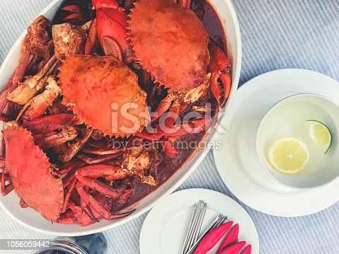 Spicy crab dish in a bowl. There are several crabs on the table. There are also crab crackers and lemon on the table.