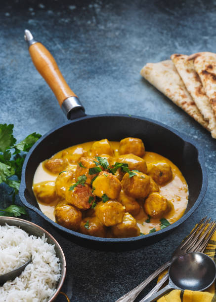 Spicy curry dish with meatballs served with pilau rice and naan bread Spicy curry dish with meatballs served with pilau rice and naan bread, selective focus curry powder stock pictures, royalty-free photos & images