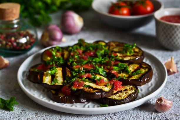 spicy eggplant with tomato sauce and cilantro. grilled eggplant. - melanzane foto e immagini stock