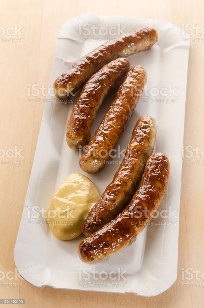 spicy grilled sausages with mustard on a square paper plate stock photo