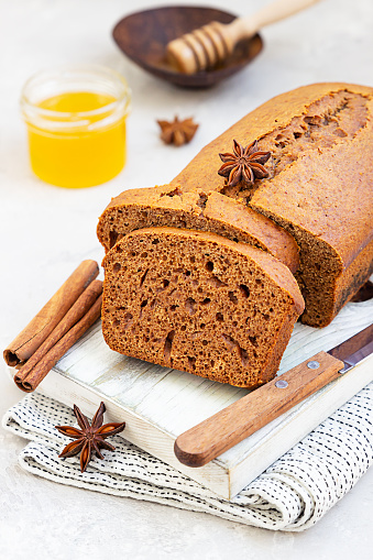 Spicy honey cake with cinnamon and anise star on light grey concrete background. Honey cake for Rosh Hashanah.