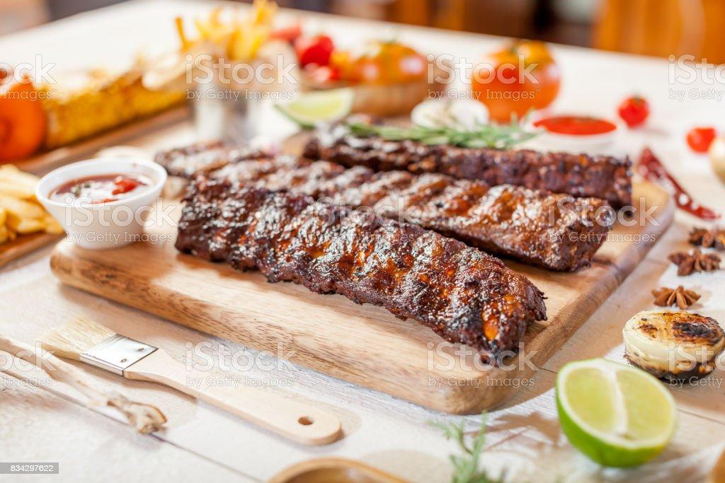 Reforços de reposição em grelhado quentes picantes de um verão que churrasco servido com batata frita, milho e tomate fresco sobre uma tábua de madeira velha - foto de acervo