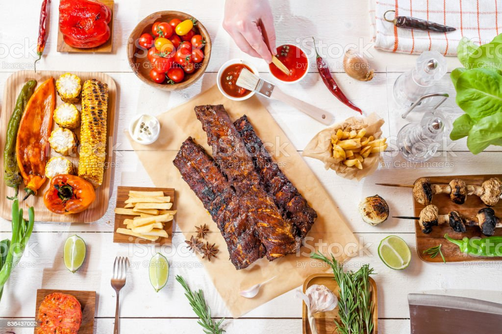 Spicy hot grilled spare ribs from a summer BBQ served with chips, corn and fresh tomatoes on an old wooden cutting board, top view stock photo