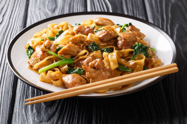 Spicy hot Thai noodles with chicken, Chinese broccoli and egg close-up on a plate. horizontal stock photo