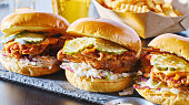 spicy nashville hot chicken sandwich with coleslaw and pickles in a row