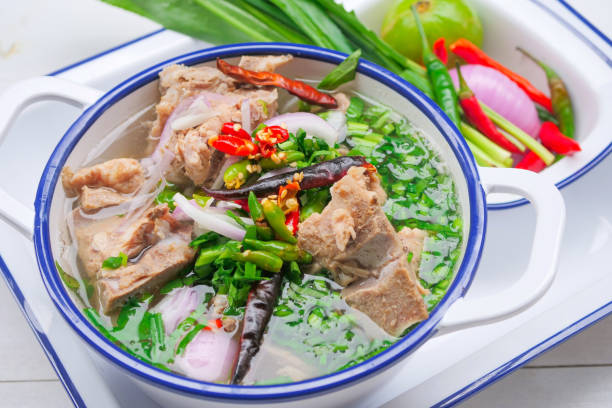 Spicy pork bone soup in Thai style Is a clear pork bone soup with large pork bones, decorated with chili and Thai herbs stock photo