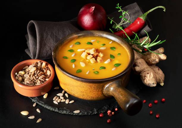 würzige kürbis creme suppe in keramischen pfanne serviert - ein topf wunder stock-fotos und bilder