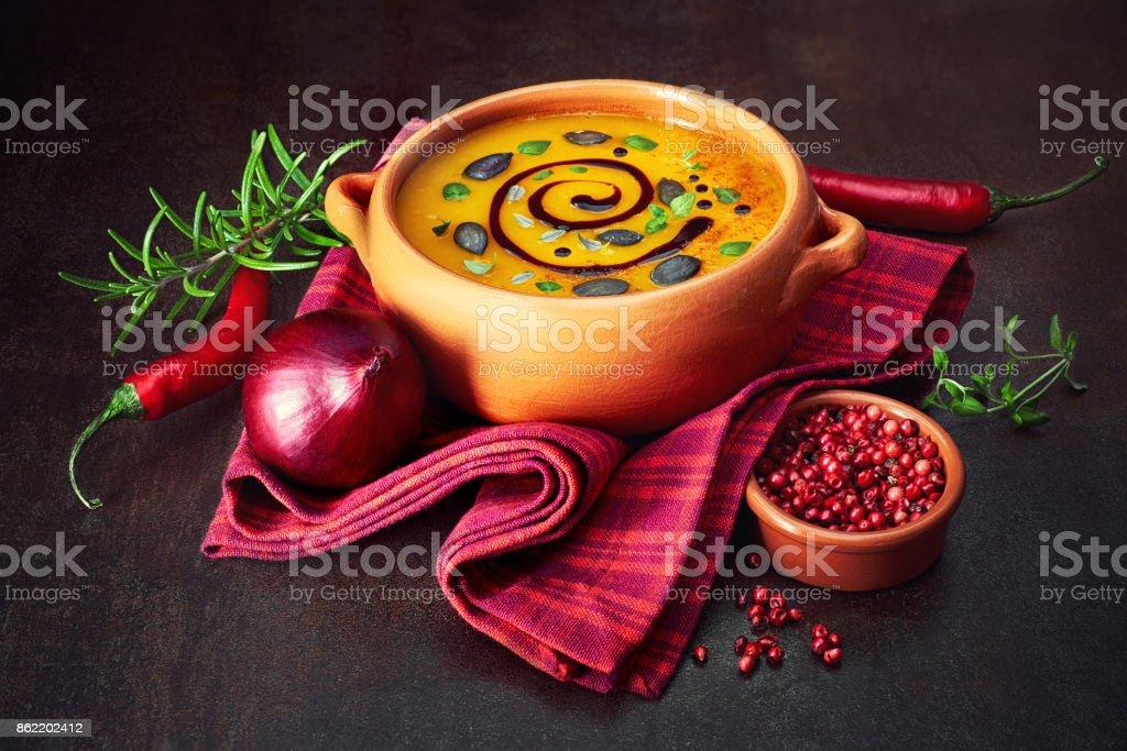 Soupe crème de citrouille épicée avec des épices autour sur fond foncé - Photo