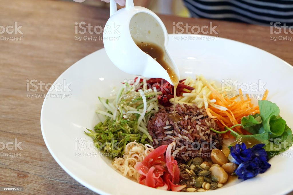 Spicy Rice Salad with variety of vegetables (carrot, winged bean, cucumber, gotu kola, beetroot, torch ginger, butterfly pea, lemon grass, macadamia, flaxseed) served with budu dressing. stock photo