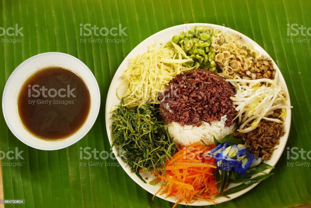 Spicy Rice Salad with Vegetable and Budu Fish sauce southern style on banana leaf from top view prepare for serving , Thai traditional royalty-free stock photo