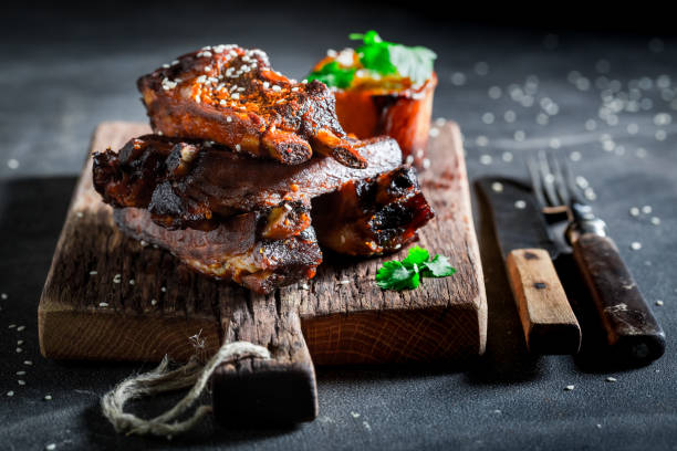 Spicy roasted ribs with potato and sesame stock photo