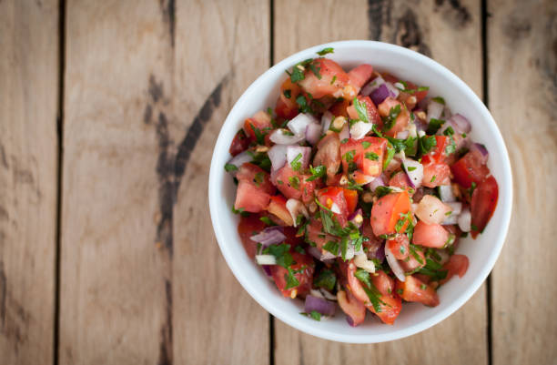 Spicy salsa dip on a wooden table, top view Salsa dip with fresh tomatoes, onions, garlic, parsley and lemon juice salsa sauce stock pictures, royalty-free photos & images