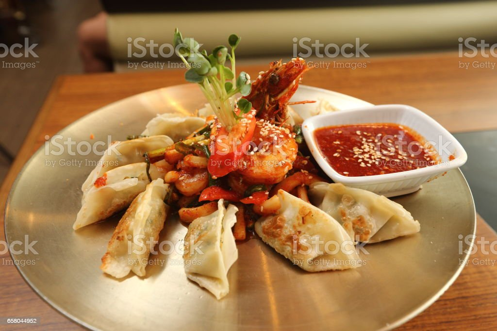 spicy seafood dumpling with hot sauce on brass round circle plate with fire oven under stock photo