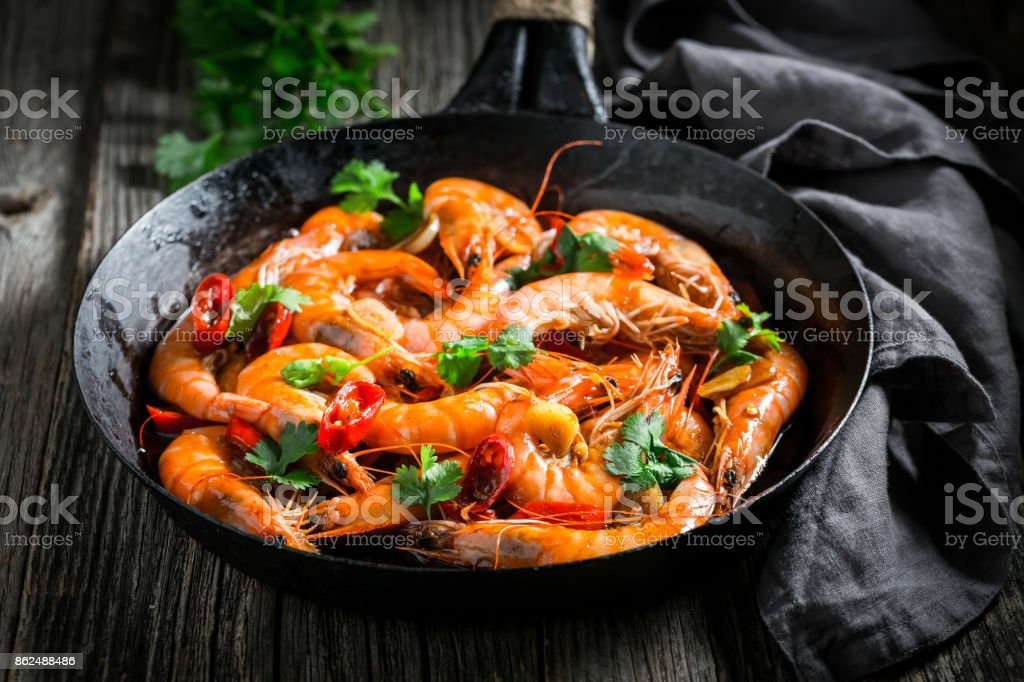 Spicy shrimps on pan with garlic, coriander and peppers stock photo