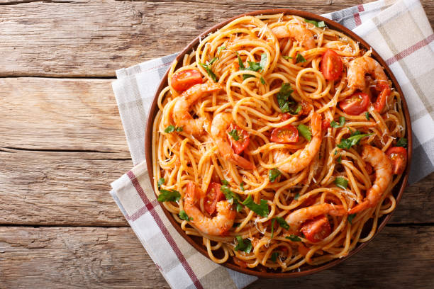Spicy spaghetti with shrimps in tomato sauce close-up. Horizontal top view from above stock photo