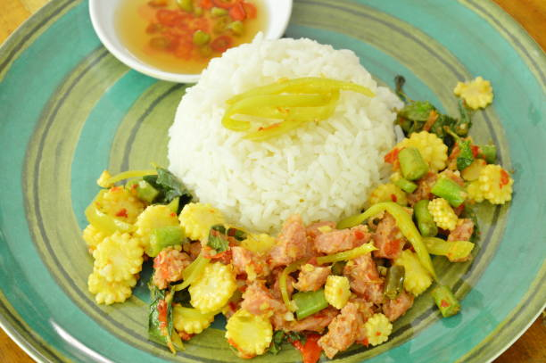 spicy stir fried fermented sour pork with basil leaf and rice stock photo