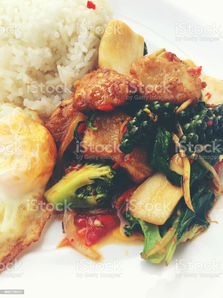 Spicy Stir Fried Fish Fillet with Thai herb with rice and fried egg in white dish on white background. vintage tone color. zbiór zdjęć royalty-free