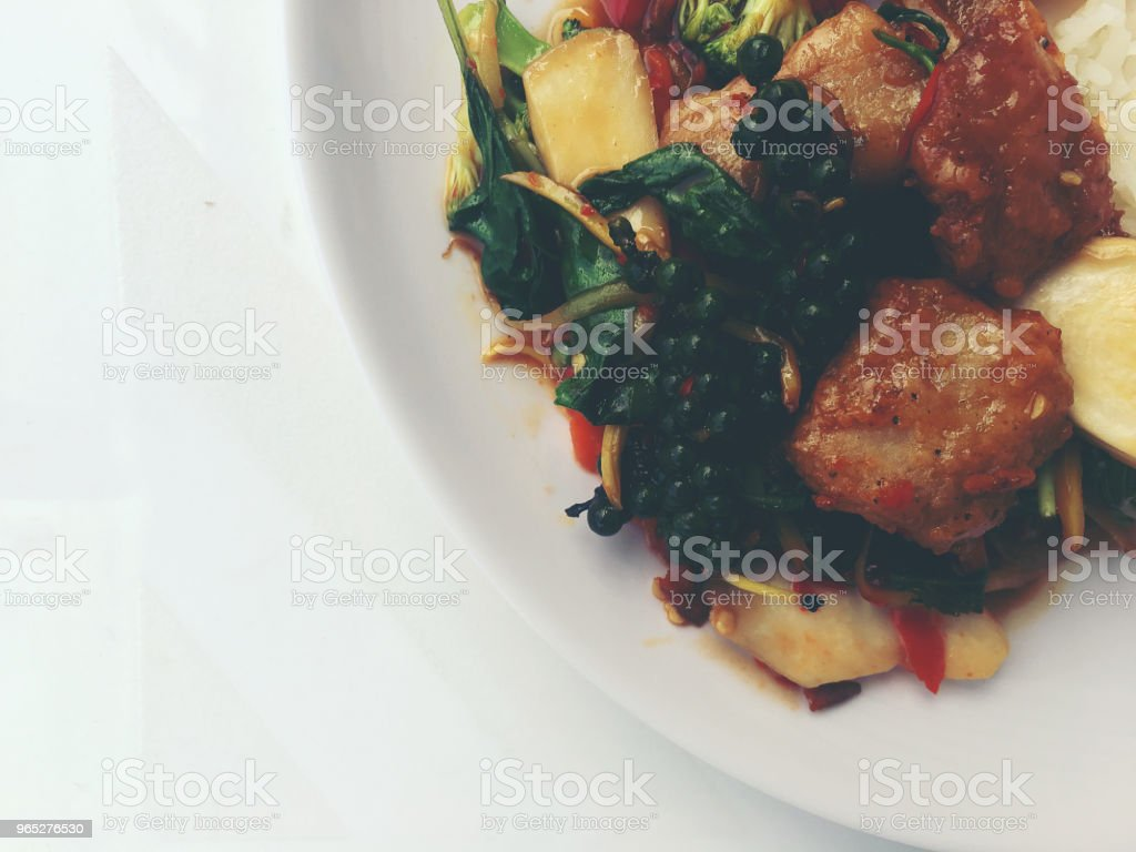 Spicy Stir Fried Fish Fillet with Thai herb with rice and fried egg in white dish on white background. vintage tone color. royalty-free stock photo