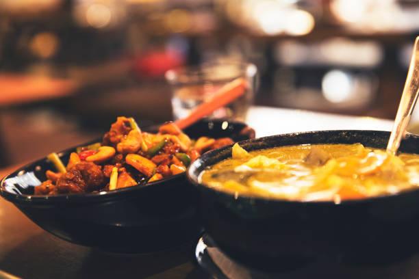 spicy thai green curry und rühren gebraten huhn auf den tisch serviert - roten küchentische stock-fotos und bilder