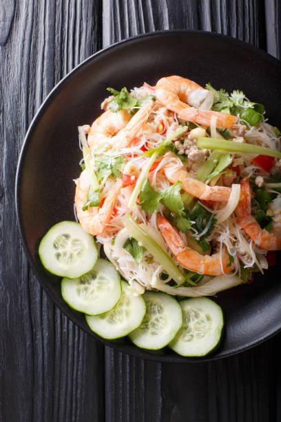 würziger yum woon sen salat mit garnelen, schweinefleisch und gemüse aus nächster nähe auf dem tisch. vertikale obere ansicht - erdnusssalatdressings stock-fotos und bilder